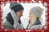 Cute couple in warm clothing hugging against snow