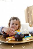 Composite image of Smiling little girl eating confectionery at home with snow falling