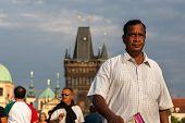 Indian tourist walks on Charles Bridge, Prague, Czech Republic