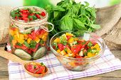 Vegetable salad in glass jar and bowl on wooden table, on bright background