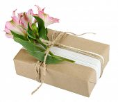 Natural style handcrafted gift box with fresh flowers and rustic twine, isolated on white