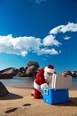 Father Christmas taking something out of his Cooler while relaxing on the beach on holiday