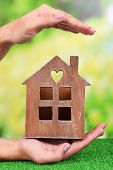 Woman hand holding small house on grass on bright background