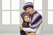 Mother and daughter in winter hats and scarf