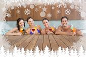 Cheerful people with drinks in swimming pool against fir tree forest and snowflakes