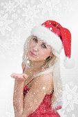 Woman wearing santa hat as she blows kiss against snowflakes on silver