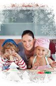 Cheerful mother baking with her children against christmas frame
