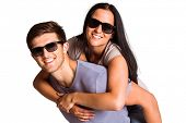 Man giving his pretty girlfriend a piggy back on white background
