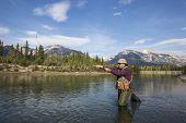 foto of fly rod  - fisherman fly fishing in a mountain river - JPG