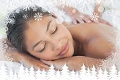Beautiful brunette enjoying a massage against fir tree forest and snowflakes