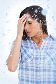 Composite image of Woman with a headache and hand on forehead with snow falling