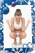 Successful young woman crouching on a scales against christmas frame