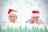 Festive mature couple smiling at camera against snowflakes and fir trees in green