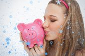 Close up of a young woman kissing a piggybank against snow falling