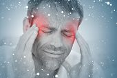 Composite image of man having a headache against snow
