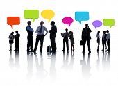 Group Of Business People Discussing And Multi-Colored Speech Bubbles Above Them.