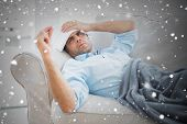 stock photo of blanket snow  - Composite image of sick man lying on sofa checking his temperature under a blanket against snow falling - JPG
