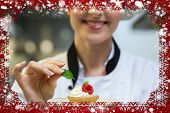 Smiling head chef putting mint leaf on little cake on plate against snow