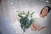 Composite image of flowers are brought to patient against snow