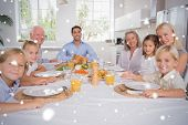 Composite image of Family celebrating thanksgiving against snow falling