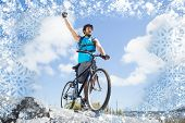 Fit man cycling on rocky terrain and cheering against snow