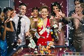 People throwing chips and cash on roulette table against snow falling