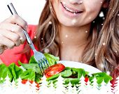 Close up of a delighted woman is eating a salad against snow falling