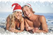 Couple lying on beach wearing christmas hats against fir tree forest and snowflakes