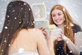Composite image of Beautiful young blond receiving a gift box on sofa against snow falling