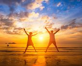 Couple in love jumping on the ocean beach during amazing sunset . Long-awaited vacation concept and romantic honeymoon.