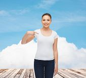 gesture, vacation, advertising and concept - smiling young woman in blank white t-shirt pointing finger on herself over wooden berth and blue sky background