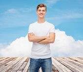 t-shirt design, advertising, vacation and people concept - smiling young man in blank white t-shirt over wooden berth and blue sky background