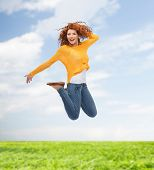 happiness, freedom, movement, summer and people concept - smiling young woman jumping in air over natural background