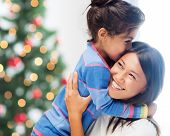 family, children, christmas, x-mas and happy people concept - hugging mother and daughter