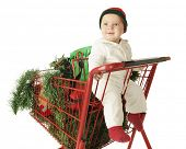 An adorable baby boy happily riding in the child's seat of a red shopping cart that's filled with holiday goodies.  On a white background.