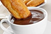 closeup of a cup of xocolata i melindros, hot chocolate with typical pastries of Catalonia, Spain