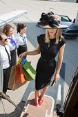 Full length of rich woman carrying shopping bags while boarding private jet with pilot and airhostes