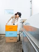 Female beekeeper with stacked honeycomb crates working in beekeeping factory