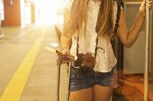 Young tourist girl with photocamera, boarding a train at a railway station. European Tour.