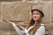 Cute young girl near a wall painted chalk heart and arrow. Falling in love concept.