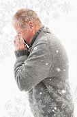 Sick mature man blowing his nose against snowflakes
