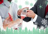 Close up of two colleague drinking champagne to celebrate christmas against snowflakes and fir trees in green