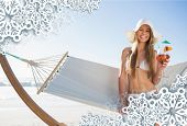 Smiling blonde wearing sunhat sitting on hammock with cocktail against snowflake frame