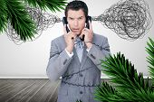 Overworked businessman holding two telephones against digitally generated fir tree branches