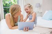 Cute little girl and mother on bed using tablet at home in the bedroom