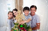 Happy little kid decorating a Christmas tree with his family against snow falling