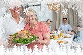 Grandparents holding chicken roast with family at dining table against fir tree forest and snowflakes