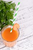 Glass of carrot juice with parsley on wooden background