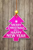 A beautiful pink christmas tree tag on a wooden background happy new year