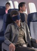 Young woman sleeping on airplane with eye mask